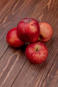 Vista lateral de maçãs vermelhas na superfície de madeira