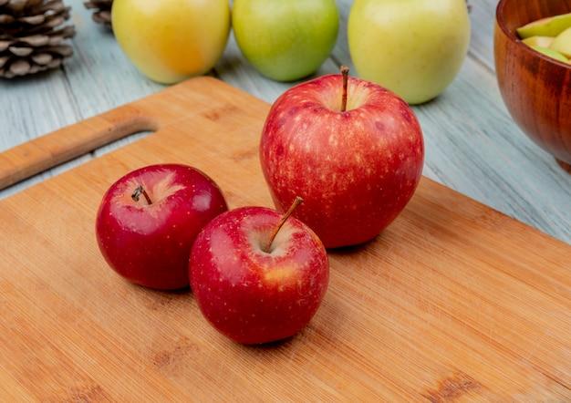 Vista lateral de maçãs vermelhas na tábua com amarelos e verdes sobre fundo de madeira