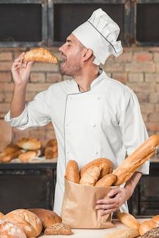 Vista lateral, de, macho, padeiro, comer, fresco, croissant, segurando, loaf, de, pães