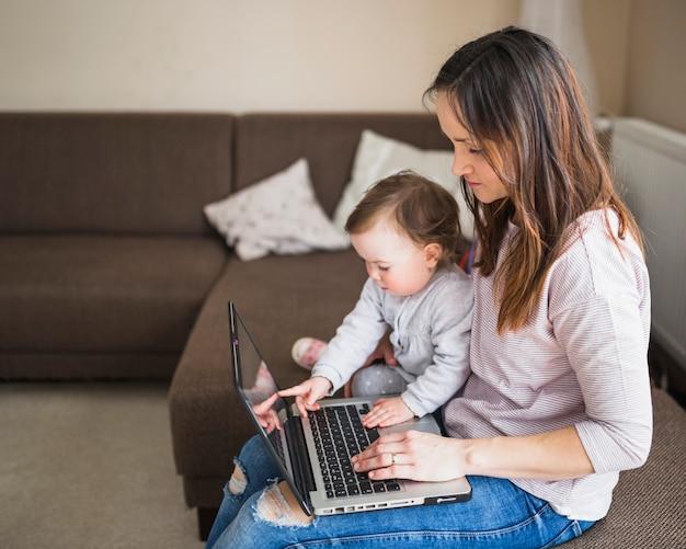 Vista lateral, de, mãe, com, dela, criança, sentar sofá, usando computador portátil