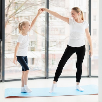 Vista lateral de mãe e filha exercitando em casa