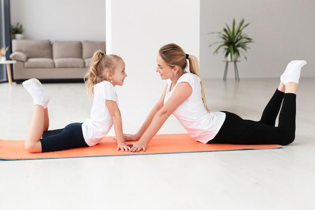 Vista lateral de mãe e filha exercitando na esteira da ioga em casa