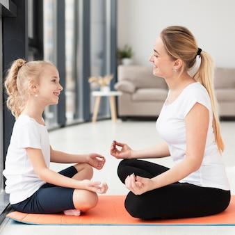 Vista lateral de mãe e filha fazendo uma pose de ioga em casa