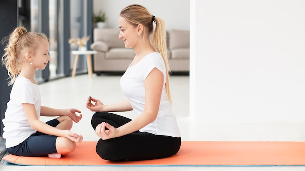 Vista lateral de mãe e filha fazendo yoga em casa com espaço de cópia