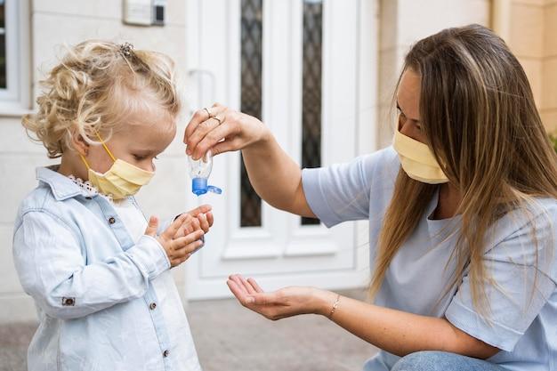 Vista lateral de mãe e filho com máscaras médicas e desinfetante para as mãos