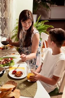 Vista lateral de mãe e filho na mesa de jantar