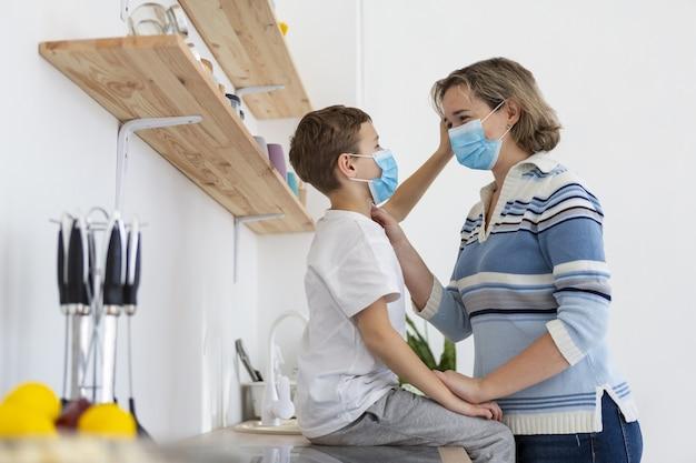 Vista lateral de mãe e filho usando máscaras médicas
