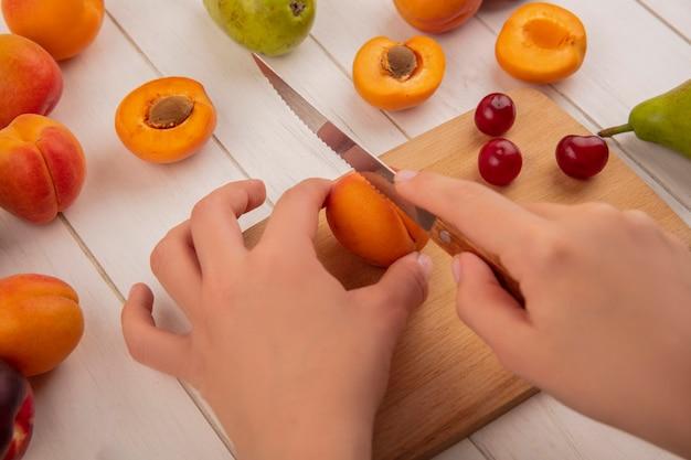 Vista lateral de mãos cortando pêssego com faca e cerejas na tábua com padrão de pêssegos peras em fundo de madeira