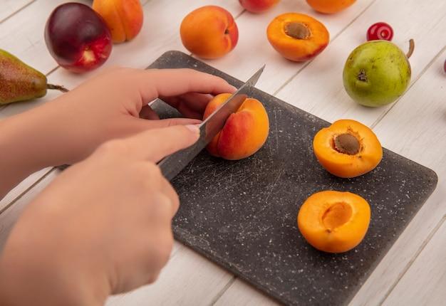 Vista lateral de mãos cortando pêssego com uma faca e meio corte de pêssego em uma tábua com padrão de peras e pêssegos em fundo de madeira