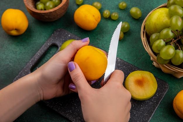 Vista lateral de mãos femininas cortando nectacota com faca e meio corte de pluot na tábua e pluot de uva na cesta com bagas de uva em uma tigela sobre fundo verde