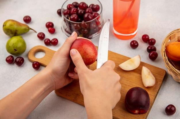 Vista lateral de mãos femininas cortando pêssego com faca na tábua e suco de cereja com jarra de cereja e cesta de damasco com peras no fundo branco