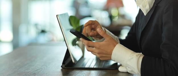 Vista lateral de mãos femininas usando o smartphone enquanto trabalhava com o tablet em cima da mesa no café