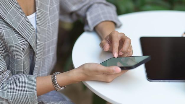 Vista lateral de mãos femininas usando smartphone na mesa de centro com tablet no café