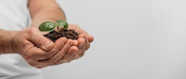 Vista lateral de mãos masculinas segurando solo e planta com espaço de cópia