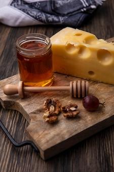 Vista lateral de mel em um pote de queijo e nozes com uvas em um suporte