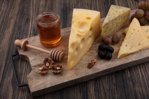 Vista lateral de mel em uma jarra com diferentes queijos e nozes com uvas em uma barraca