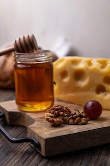 Vista lateral de mel em uma jarra com queijo e nozes em um suporte