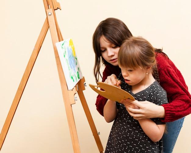 Vista lateral, de, menina, ajudando, menina, com, baixo, síndrome, pintura