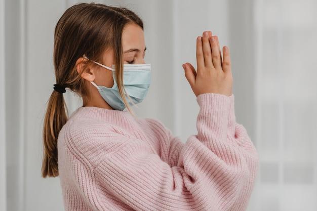 Vista lateral de menina com máscara médica rezando
