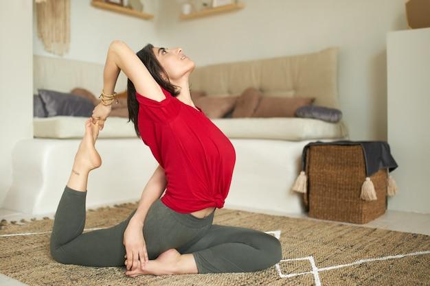 Vista lateral de menina descalça desportiva com corpo forte e flexível, exercitando-se em casa