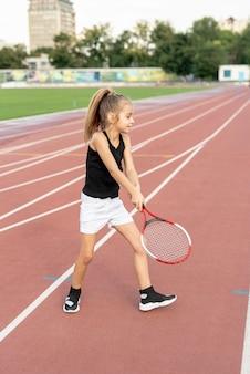 Vista lateral, de, menina, jogando tênis