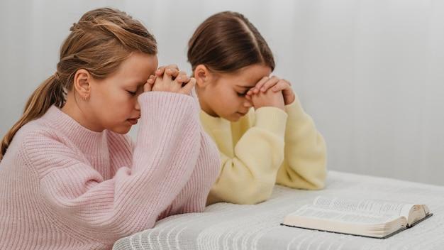 Vista lateral de meninas orando em casa com a bíblia