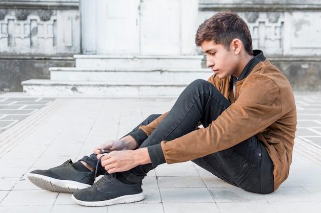 Vista lateral, de, menino adolescente, sentando, exterior, e, amarrando, seu, sapatos, renda