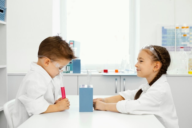 Vista lateral de menino e menina cientistas no laboratório com óculos de segurança