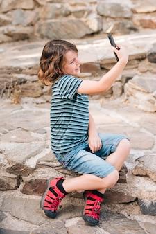Vista lateral, de, menino, fazendo exame um selfie