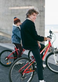Vista lateral de meninos ao ar livre na cidade com suas bicicletas