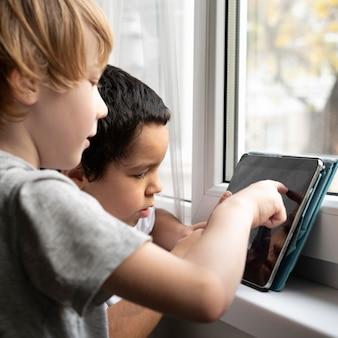 Vista lateral de meninos brincando em um tablet em casa