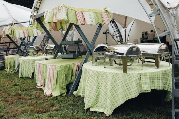Vista lateral de mesas servidas no jardim para festa