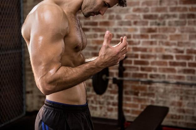 Vista lateral de mestra de um homem mostrando seu corpo no ginásio
