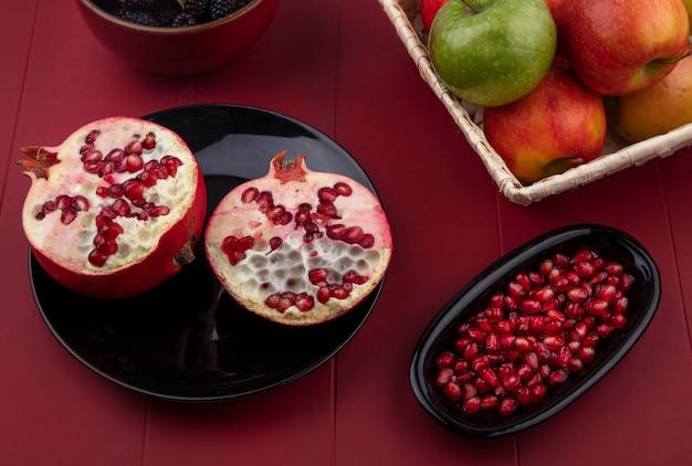 Vista lateral de metades de romãs em uma placa preta com maçãs coloridas em uma cesta em uma superfície vermelha