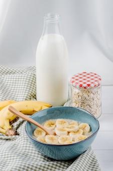 Vista lateral de mingau de aveia com banana em uma tigela de cerâmica e uma garrafa de vidro de leite na mesa rústica