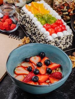 Vista lateral de mingau de aveia com fatias de morangos e mirtilos em uma tigela de cerâmica em cima da mesa
