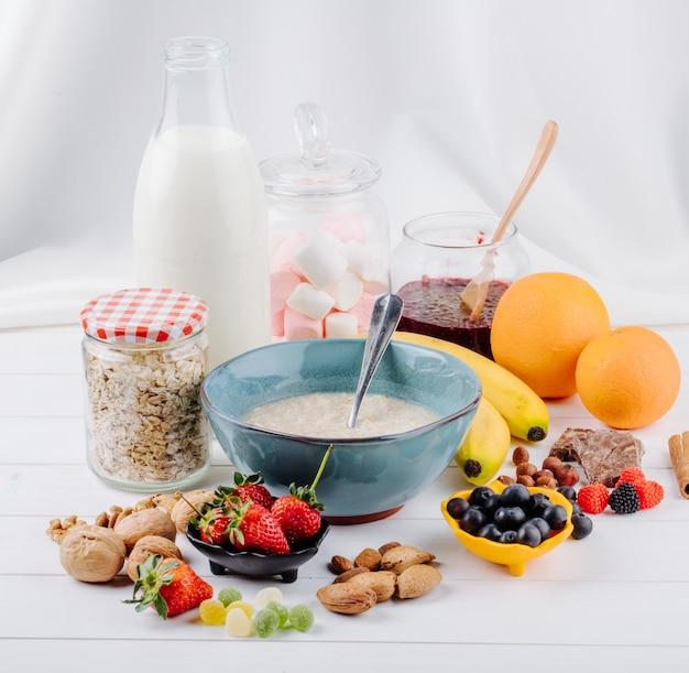Vista lateral de mingau de aveia em uma tigela e frutas frescas banana laranjas e nozes na mesa rústica branca