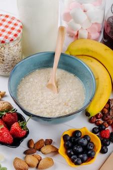 Vista lateral de mingau de aveia em uma tigela e frutas frescas de bananas e nozes na mesa rústica branca