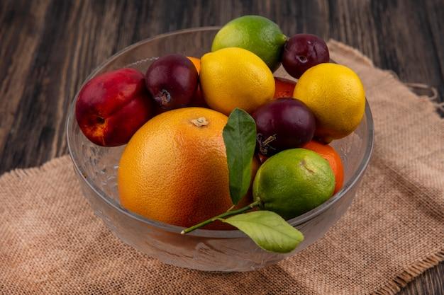 Vista lateral de mix de frutas limões, limas, ameixas, pêssegos e laranjas em um vaso em um guardanapo bege