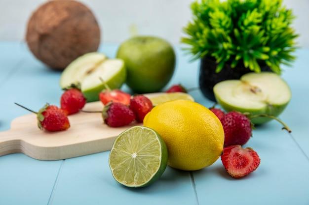 Vista lateral de morango em uma mesa de corte de cozinha com limão e coco em um fundo azul