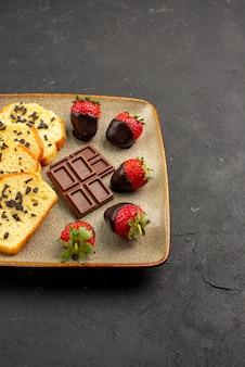 Vista lateral de morangos distantes e bolo de chocolate com apetitosos morangos vermelhos com cobertura de chocolate no prato à esquerda