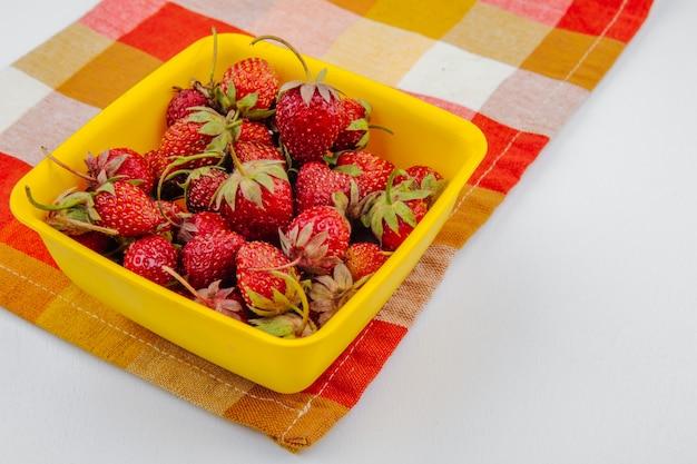 Vista lateral de morangos maduros frescos em tigela amarela no guardanapo xadrez em branco