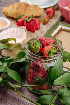 Vista lateral de morangos maduros frescos em uma jarra de vidro e croissant de folhas verdes em madeira rústica
