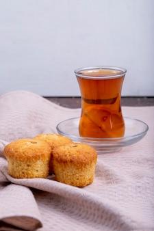 Vista lateral de muffins com armudu copo de chá numa toalha de mesa