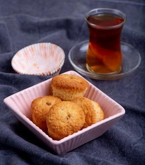 Vista lateral de muffins em uma tigela de moldes de papel e copo armudu de chá em cinza
