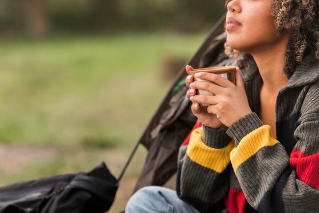 Vista lateral de mulher acampando e tomando uma bebida quente
