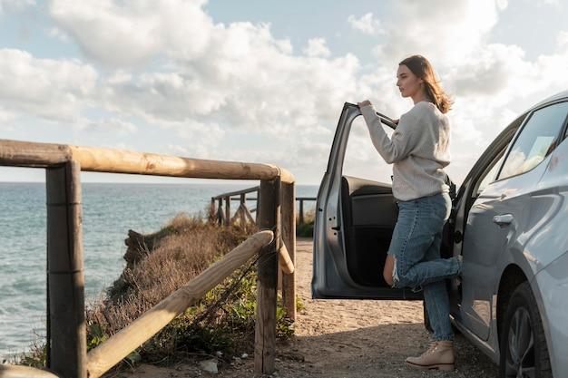 Vista lateral de mulher admirando a vista da praia de seu carro