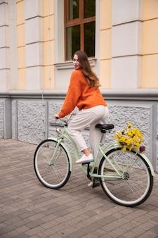 Vista lateral de mulher andando de bicicleta ao ar livre