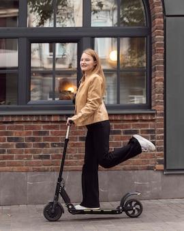 Vista lateral de mulher andando de scooter elétrica ao ar livre