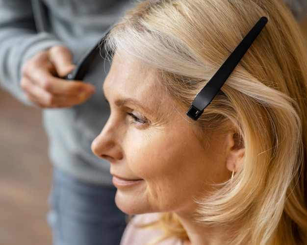 Vista lateral de mulher arrumando o cabelo em casa